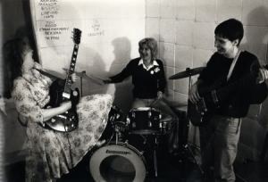 Black and white photo of band rehearsing, Steph with guitar tilted skyward, Angie on drums and Sue on bass guitar, all laughing