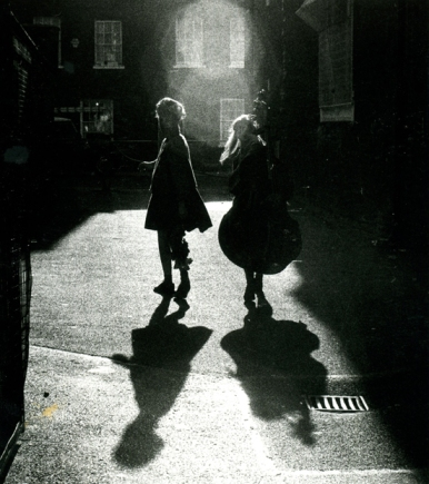 A photo taken from behind the two women as they look back over their shoulders, taken in very shadowy urban location near Waterloo station. They and the double bass are in silhouette.
