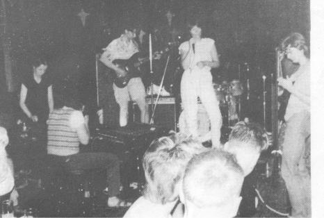 Blurry photo of the Bad Habits performing on stage: keyboard and guitar players and singer, plus some audience members dancing in front.