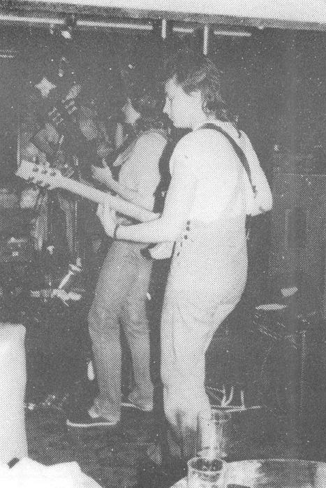 Very blurry old photo of two of the Bad Habits on stage, audience behind guitarists.