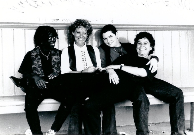 Black and white photo of band. Smiling. Lynne sat across the other three members laps.