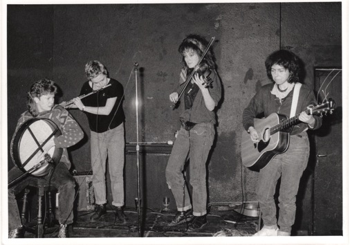 Black and white photo of band in performance, playing bodhran, flute, fiddle and guitar.