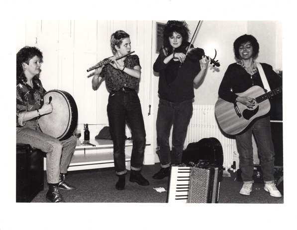 Black and white photo of Bodhrans & Binlids in performance, playing bodhran, flute, fiddle and guitar, accordian also on stage.