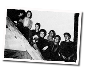Black and white photo of seven members of the Bright Girls on a staircase.
