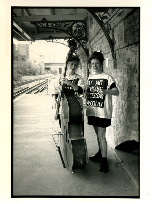 The two women standing on Ladbroke Grove tube station platform with double bass and drumsticks, both wearing t-shirts bearing the slogan 'By any means necessary' made famous by Malcolm X.