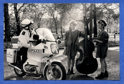 A policeman on a motorbike is shown telling the two women and their double bass to move on.