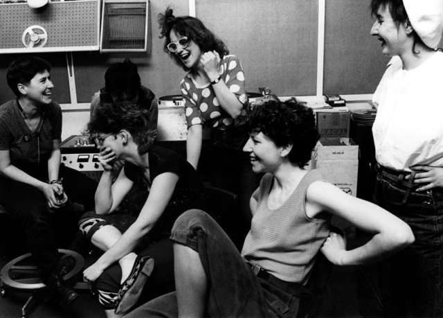 Five members of Cast Iron Fairies in a studio, listening to a recording playing back, smiling, laughing or looking thoughtful.