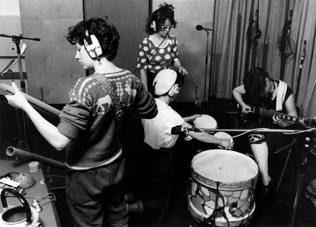 Four members of Cast Iron Fairies in recording studio, playing guitars and bongo drums and wearing earphones. Microphones and a large bass drum also shown.