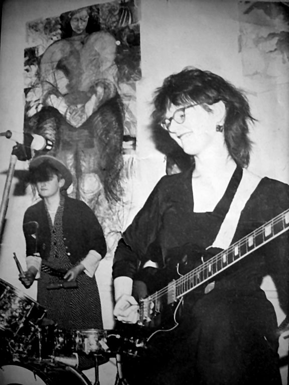 Black and white photo of two of the Cast Iron Fairies, Babs on left playing a drum kit and hand-held percussion instruments and standing behind a microphone, Jackie playing guitar and smiling. A large batik backdrop wall-hanging made by the band shows a large figure of a seated woman.
