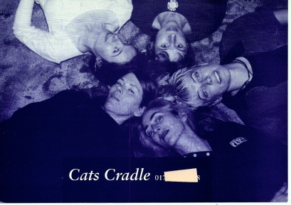 A publicity photo, in tones of blue, of the Cat's Cradle members lying in a circle with their heads at its centre, hair splayed on floor, smiling, text saying 'Cats Cradle' and contact phone number.
