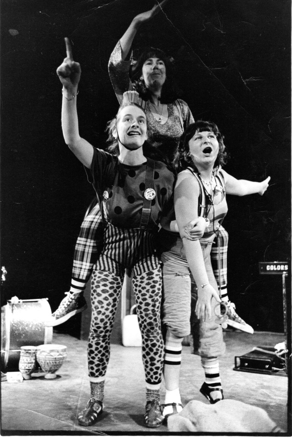 The three members of the group stand in a triangle as part of a performance. Black and white.