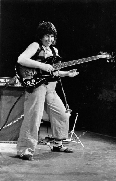 Rae Levy performs bass on stage. Black and white photo.