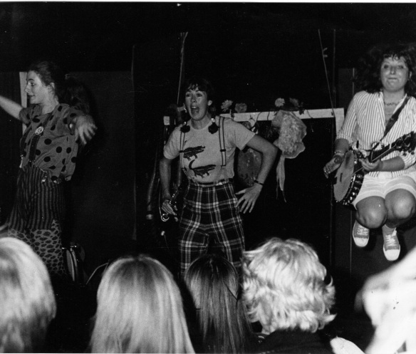 Three members of the band perform in front of a crowd. Black and white. The image includes the back of the audience's heads. Rae is jumping in the air and plays the banjo. They wear vibrant costumes.