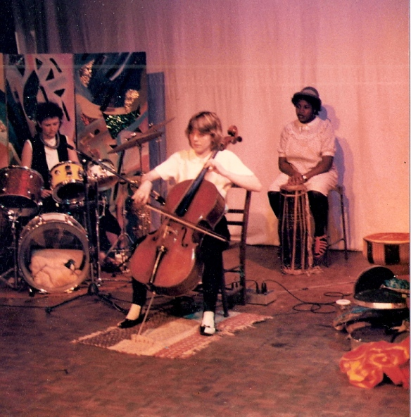 Penni playing cello in centre of photo, Donna behind her with hand drum and Jilly playing drum kit. Hand-painted screens in background and costumes and instruments scattered around.