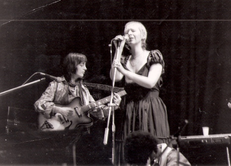 Black and white photo of group performing with Sally on guitar, Donna in background on congas, Maggie singing. Microphones and keyboard also in photo.