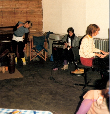 Val  dancing expressively, Sally on guitar and Maggie playing piano, with microphones, amplifiers and costumes also in photo.