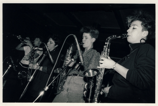 First of four black and white photos of the Deltones first gig, at London's Sol y Sombre club, shows three women saxophone players and a trumpeter blowing strongly into microphones.