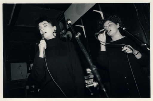 Second of four photos taken during Deltone's first gig, of two women singing into microphones.