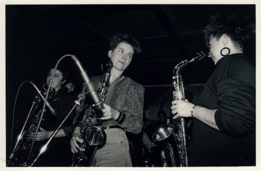Third photo of the Deltones' first gig shows two saxophone players looking at each other and smiling.