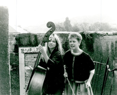 The two women performing at an outdoor venue, with double bass and percussion.