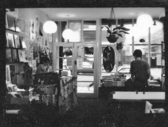 Photo from back of shop toward street window shows array of books and records.