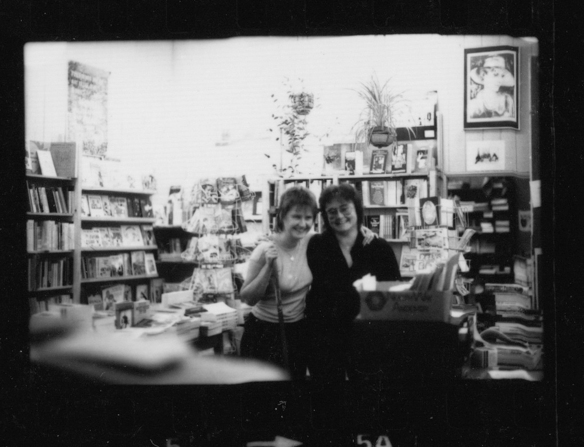 Two women workers at Sisterwrite smiling, lots of bookshelves and posters in background.