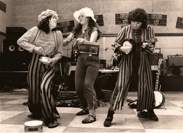 Black and white photo of the band performing music. Caroline plays a tea cup, Rix plays a washboard and Rae plays a mini banjo.