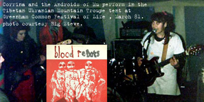 Picture of Androids of Mu playing at Greenham Common Festival of Life 1981. Includes an image of Blood Robots album cover. Red and white Monica Sjoo painting.
