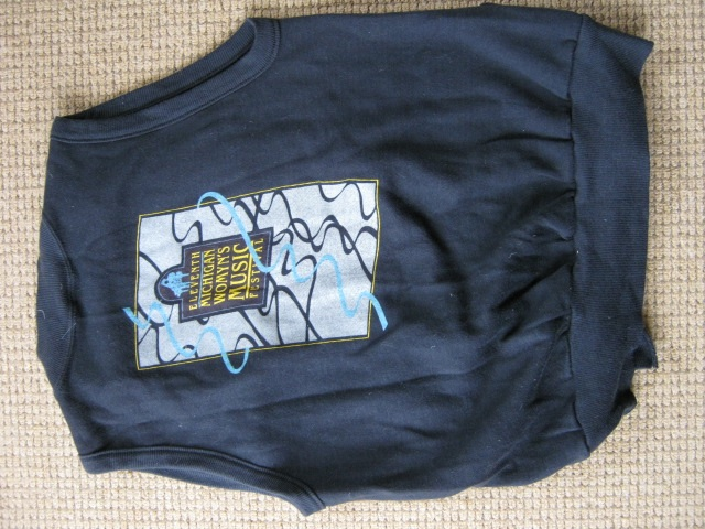 Picture of sleeveless, navy blue t-shirt, yellow and blue design on front says '11th Michigan Womyn's Music Festival