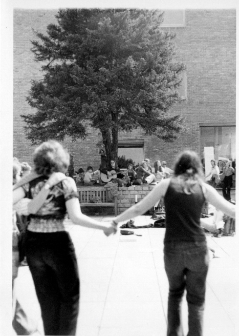 Women dancing in a huge outdoor circle, Susan with guitar in background under a tree, women are smiling and laughing, holding hands.
