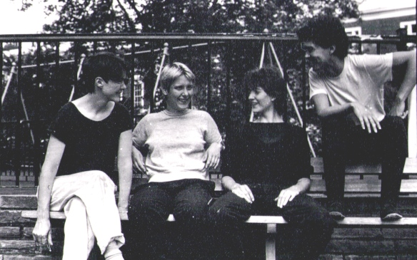 The four women in a black and white photo in a children's playground, smiling and seated on a bench, talking to one another.