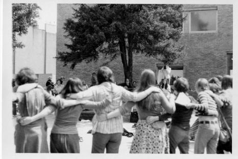Women dancing in  huge circle as Susan sings and plays guitar
