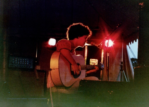 A colour photo of Georgette Okey on stage, playing her acoustic guitar in a marquee, with bright red lighting, daytime sky just visible through the tent door in the background..
