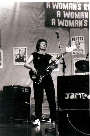 Black and white photo of Alison, Jam Today's bass player, in perfomance. Amplifiers and microphones around the stage and posters pinned on a backdrop. One is a 'WANTED' poster in the style of the American 'Wild West' with a picture of Maggie Thatcher. A large banner above the stage reads 'A WOMAN'S RIGHT TO INDEPENDENCE, A WOMAN'S RIGHT TO WORK, A WOMAN'S RIGHT TO CHOOSE.'