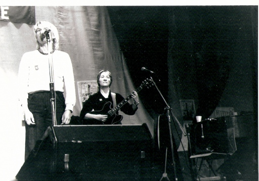 Jam Today performing at a Festival for Women's Rights. Barbara is singing into a microphone at the front of the stage, Terry playing guitar behind her, with large amplifiers in front of them.