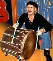 Colour photo of Josefina laughing, crouching down and playing a large Rajasthani drum with sticks, with an acoustic guitar in background.