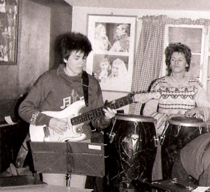 Deirdre playing guitar at a Guest Stars rehearsal, looking seriously at her fret board while Linda playing congas watches her.