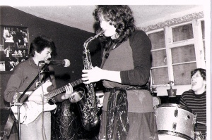 Guitarist and drummer are laughing with each other while playing, behind saxophonist Ruthie who is playing intently.