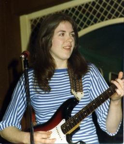 A colour pic from a pub gig by Painted Lady shows Deirdre Cartwright playing an electric guitar and smiling.