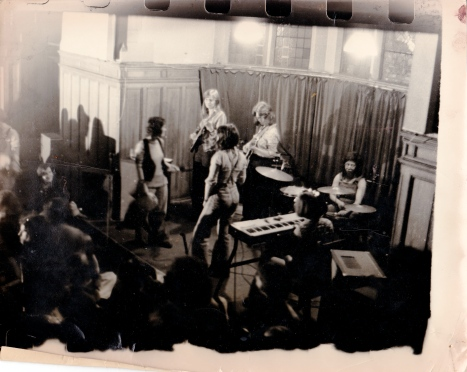 A faded photo taken from above shows the whole band on stage, with Luchia the singer turned back towards the guitarist.