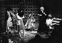 Black and white photo of five Feminist Improvising Group members, playing trumpet, double bass, keyboards and singing, a performance in action.