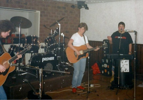 The four Fabulous Jam Tarts in concert. two guitarists at front of stage with clarinet player, drums behind.