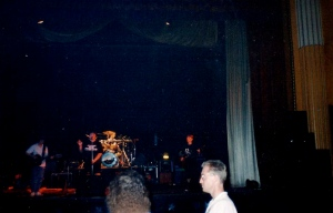 A live gig on stage with spotlights on the band and audience dancing in front.