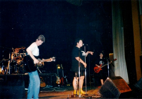Photo taken from the stage wings shows singer and bas guitarist performing to front, drummer and guitarist behind. Singer wearing shorts and yellow doc Marten boots.