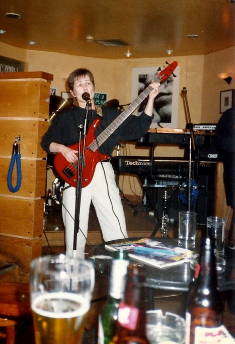 bass player on stage, playing and singing, pints of beer on table in front of stage indicate a pub gig.