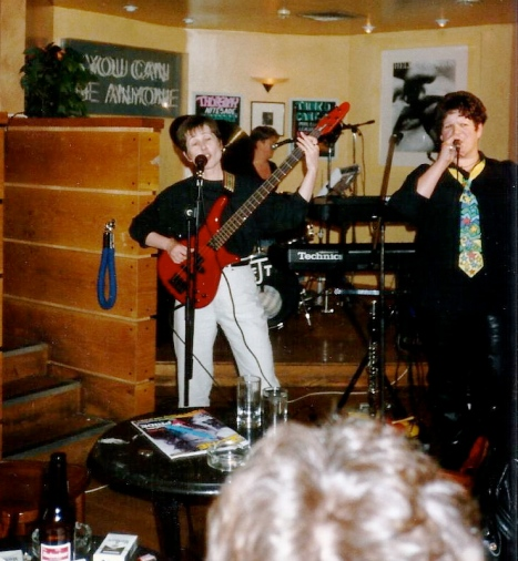 bass guitarist and lead singer on stage at a pub gig