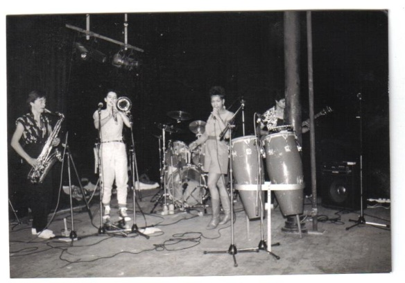 Grainy, black and white photo of band performing live on a stage. Conga drums in the foreground.
