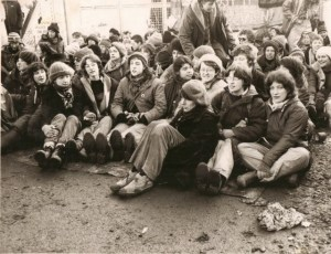Deb and Dorry hold hands at a sit down protest with many other women at Greenham. Black and white photo.