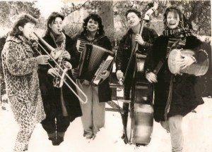 Black and white photo of the Fabulous Dirt Sisters. Outside with instruments. Smiling and happy.