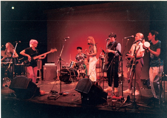 Hi Jinx in a lively performance on stage showing percussionist, bassist, drummer, guitarist and horn section players on a large stage, under bright red lighting, with amplification equipment.